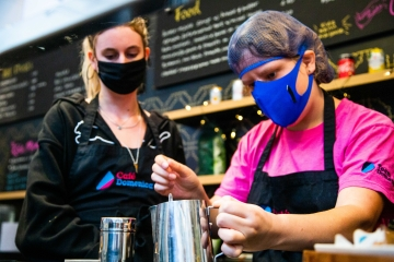 Woman makes coffee with another woman looking on
