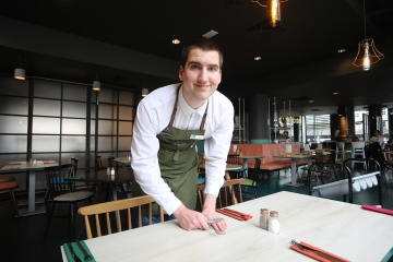 Smiling young man waiter looks up from laying restaurant table